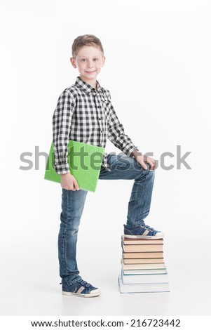 Happy schoolboy with books isolated on white background. Cute boy standing on pile of books  - stock photo