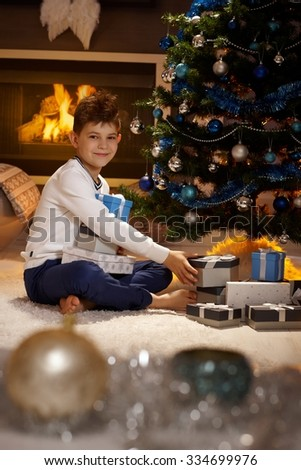 Happy schoolboy with christmas presents, sitting on floor, looking at camera. - stock photo