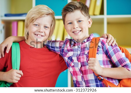 Happy schoolboys with backpacks looking at camera