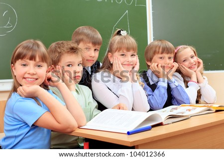 Happy schoolchildren at a classroom. Education. - stock photo