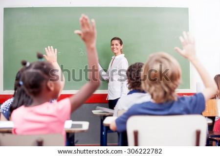 Happy schoolchildren at primary school raising hand in elementary multi ethnic classroom. - stock photo