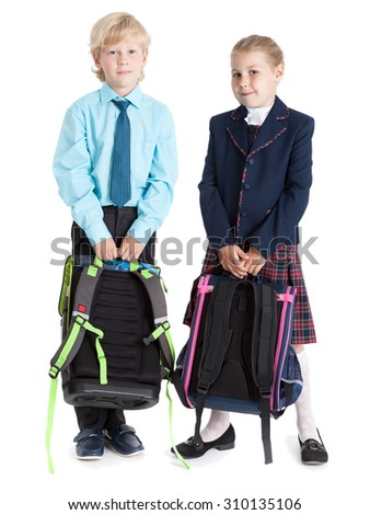 Happy schoolchildren in school uniform holding schoolbags in hands, full length, isolated on white background - stock photo
