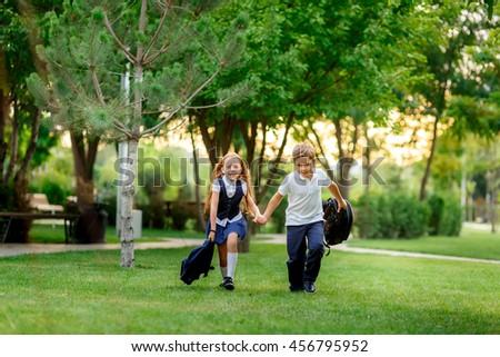 happy schoolchildren running in the park after school. waving backpacks. - stock photo
