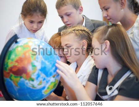 Happy schoolchildrensearching country on the globe - stock photo