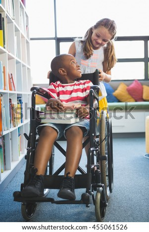 Happy schoolgirl carrying schoolboy in wheelchair at library