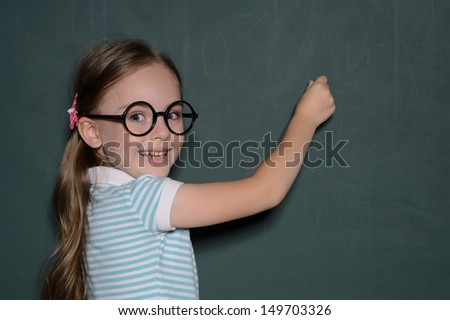 Happy schoolgirl. Cheerful little schoolgirl in glasses standing near the blackboard and looking over shoulder - stock photo