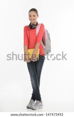 Happy schoolgirl. Happy teenage schoolgirl holding with book bag holding a book and smiling at camera while standing isolated on white