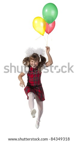 Happy schoolgirl jumping on a white background with colorful balloons in his hand.