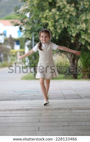 Happy schoolgirl runs during recess at school. Beautiful girl is happy. Laughing kid runs and rejoices. - stock photo