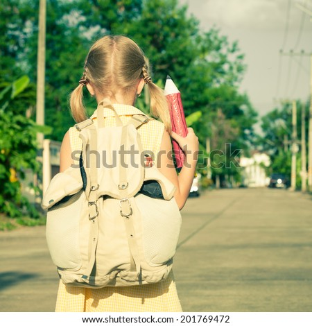 happy schoolgirl standing on the road at the day time and ready to go to school - stock photo