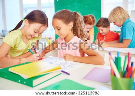 Happy schoolgirls drawing together during break - stock photo