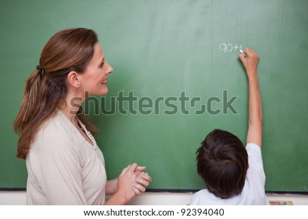 Happy schoolteacher helping a schoolboy doing an addition on a blackboard - stock photo