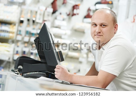 Happy seller assistant man in DIY hardware or home improvement store - stock photo