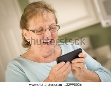 Happy Senior Adult Woman Texting on Her Smart Cell Phone in Kitchen.