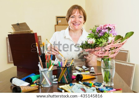 Happy senior artist in the process of painting a bouquet - stock photo