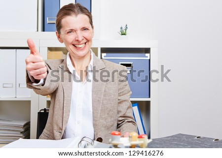 Happy senior business woman in her office holding her thumbs up - stock photo