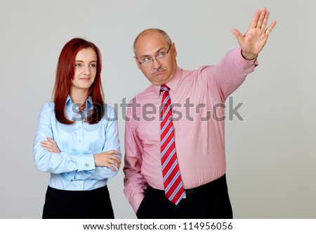 Happy senior businessman describing something young attractive businesswoman in shirts, isolated on grey - stock photo