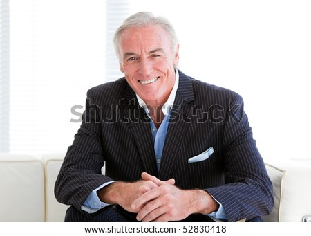 Happy senior businessman sitting on a sofa in the office - stock photo
