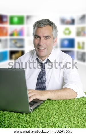 happy senior businessman working green grass desk tv presenter screen [Photo Illustration] - stock photo