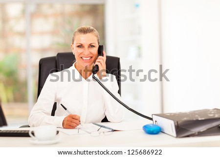happy senior businesswoman talking on the phone in office - stock photo