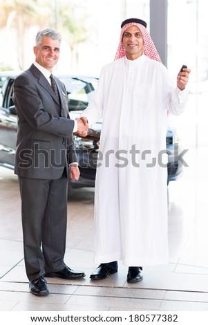 happy senior car salesman handshake with Arabic customer  - stock photo