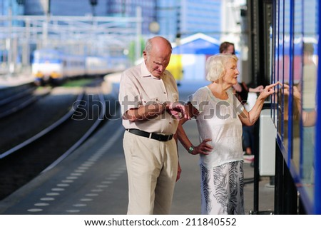 Happy senior caucasian couple traveling around Europe waiting for train in railway station platform in Amsterdam - active retirement concept  - stock photo