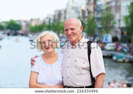 Happy senior caucasian couple traveling around Europe walking in the streets of Amsterdam, enjoying scenes of the canals on a sunny summer day - active retirement concept - stock photo