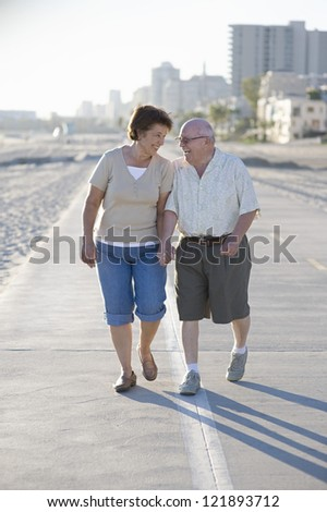 Happy senior Caucasian couple walking together in leisure time - stock photo
