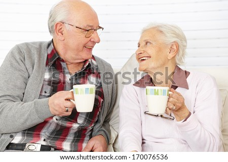 Happy senior citizen couple drinking coffee together
