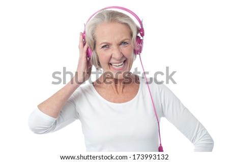 Happy senior citizen enjoying music - stock photo
