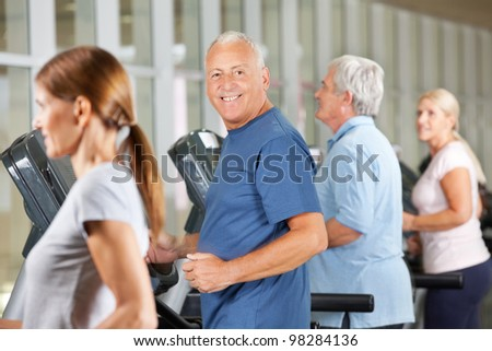Happy senior citizens jogging on treadmills in gym