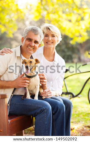happy senior couple and pet dog at the park - stock photo