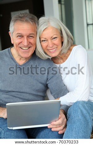 Happy senior couple connected on internet at home - stock photo