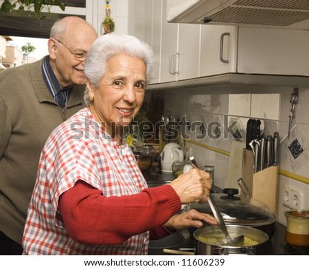 Happy senior couple cooking at home - stock photo