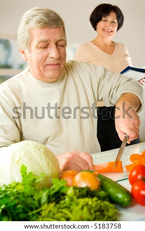 Happy senior couple cooking together at kitchen. Focus on man. - stock photo