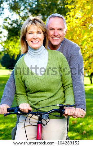 Happy Senior couple cycling in the park. - stock photo