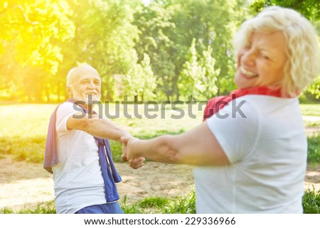 Happy senior couple dancing in a garden in sunny summer - stock photo