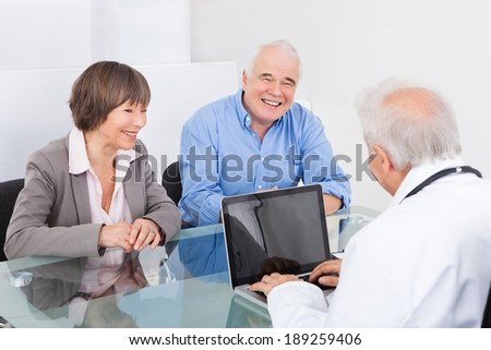 Happy senior couple discussing with male doctor at desk in hospital