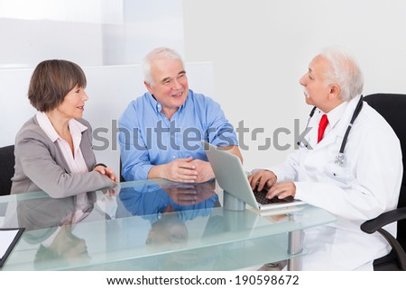 Happy senior couple discussing with male doctor in clinic
