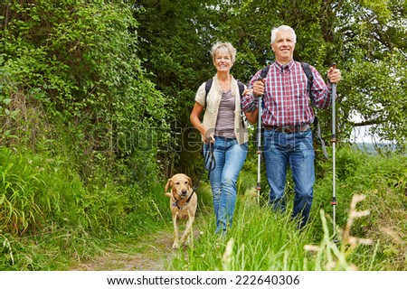 Happy senior couple doing Nordic Walking with dog in a forest - stock photo
