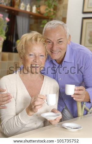 Happy senior couple drinking coffee in the kitchen. - stock photo