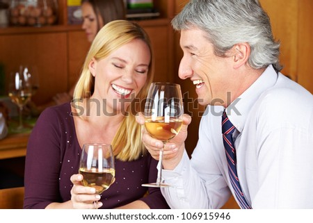 Happy senior couple drinking white wine in a restaurant