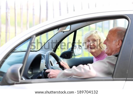 Happy senior couple driving modern car on their vacation trip - active retirement concept - stock photo
