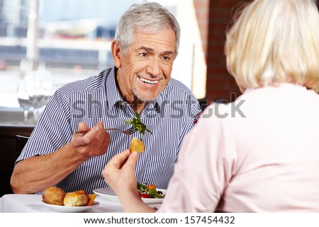 Happy senior couple eating in restaurant for lunch - stock photo