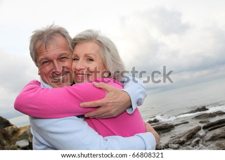 Happy senior couple embracing each other by the sea - stock photo