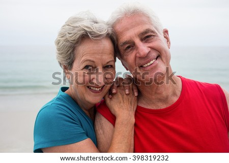 Happy senior couple embracing each other on the beach on a sunny day - stock photo