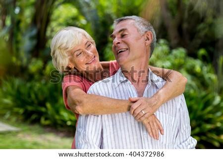 Happy senior couple embracing in yard - stock photo