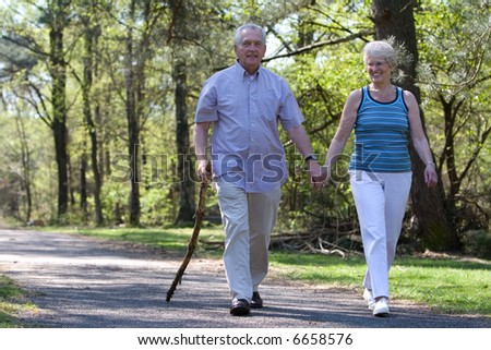 Happy senior couple enjoying a walk in the parc - stock photo