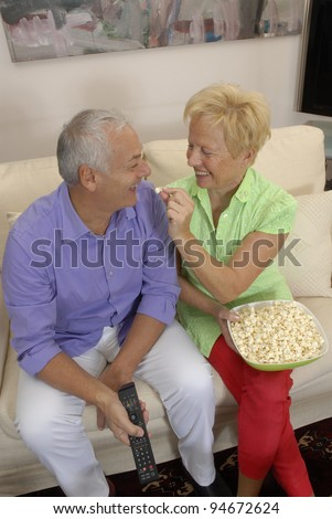 happy senior couple enjoying watching television together and eating popcorn. - stock photo