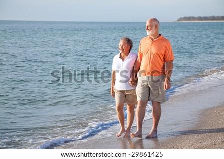 Happy senior couple enjoys a romantic stroll on the beach. - stock photo